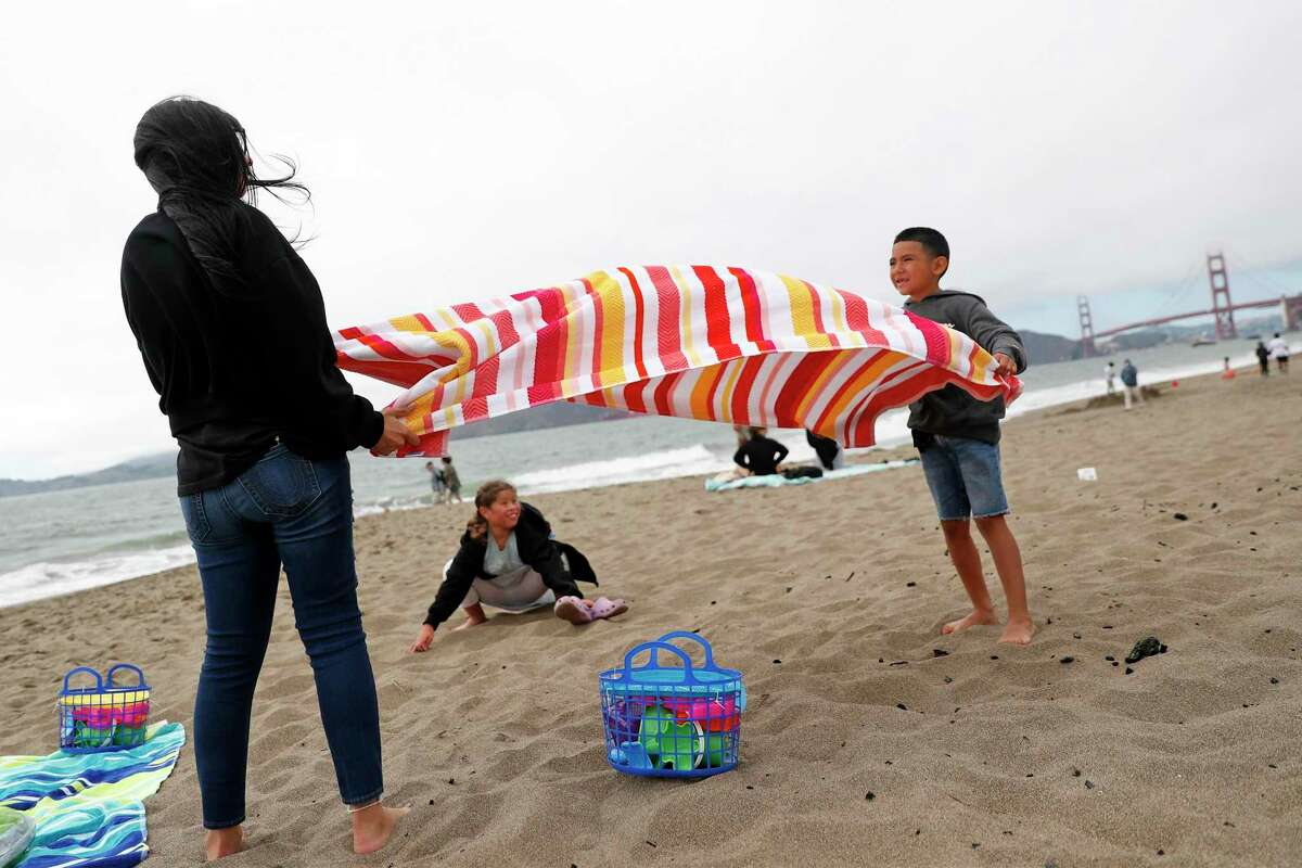 Kaydin Gonzalez, 7, and his sister, Mariah, try to fold a beach towel as the wind gusts at Baker Beach in San Francisco, Calif., on Sunday, June 27, 2021.