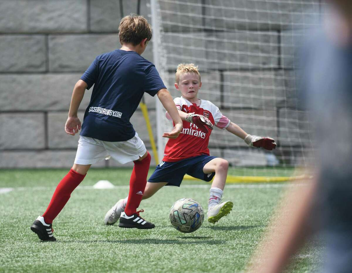 Cameron Putnam, 8, plays goalkeeper during a drill at the Cardinal Soccer Camps at Cos Cob Park in the Cos Cob section of Greenwich, Conn. Monday, July 26, 2021. About 100 elementary through high school aged boys and girls take part in the camp, which in broken up into weeklong sessions from late June through late August. Several local soccer coaches teach a variety of skills for all skill levels at the camps.