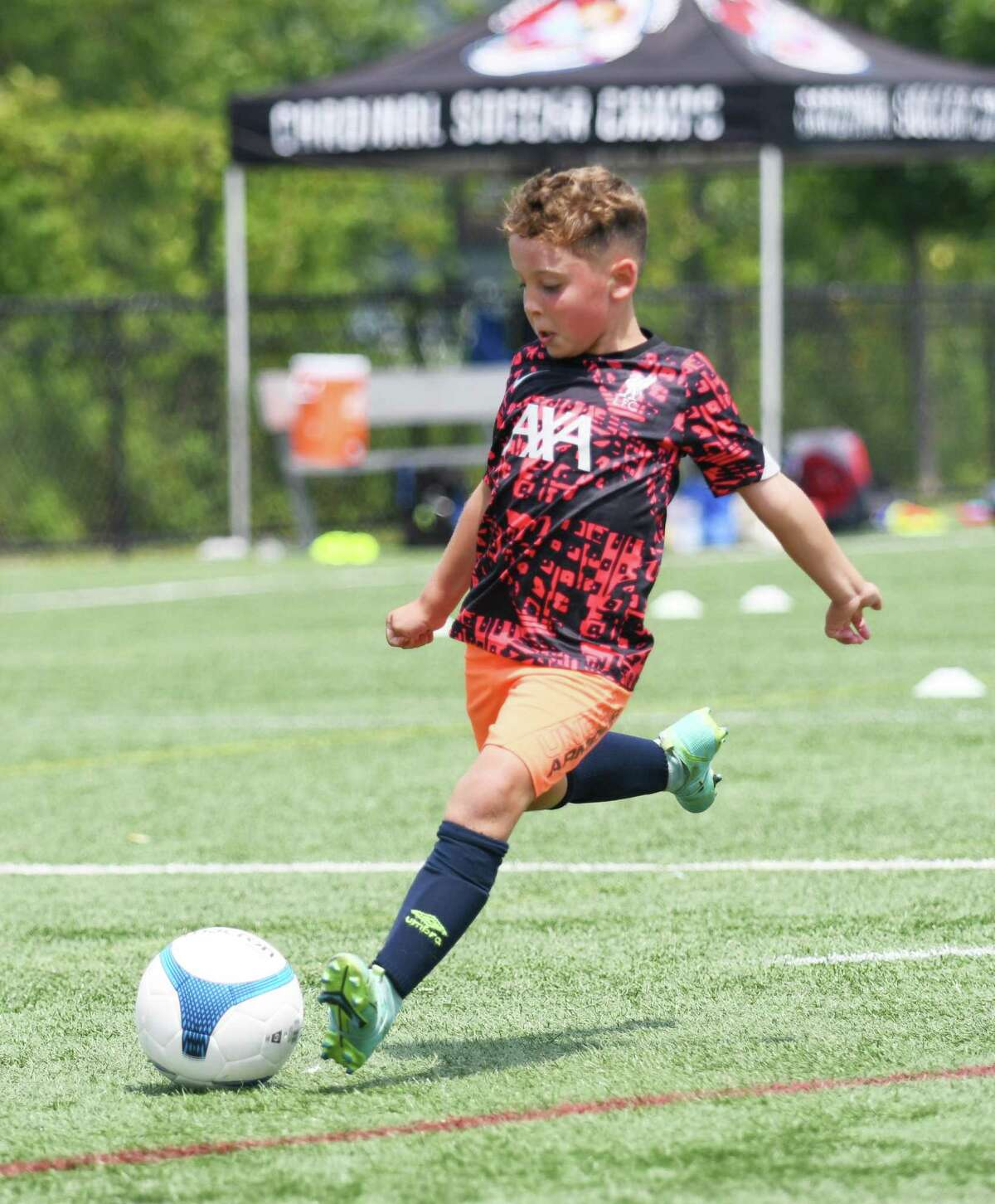 Keden Smith, 8, shoots the ball during a drill at the Cardinal Soccer Camps at Cos Cob Park in the Cos Cob section of Greenwich, Conn. Monday, July 26, 2021. About 100 elementary through high school aged boys and girls take part in the camp, which in broken up into weeklong sessions from late June through late August. Several local soccer coaches teach a variety of skills for all skill levels at the camps.