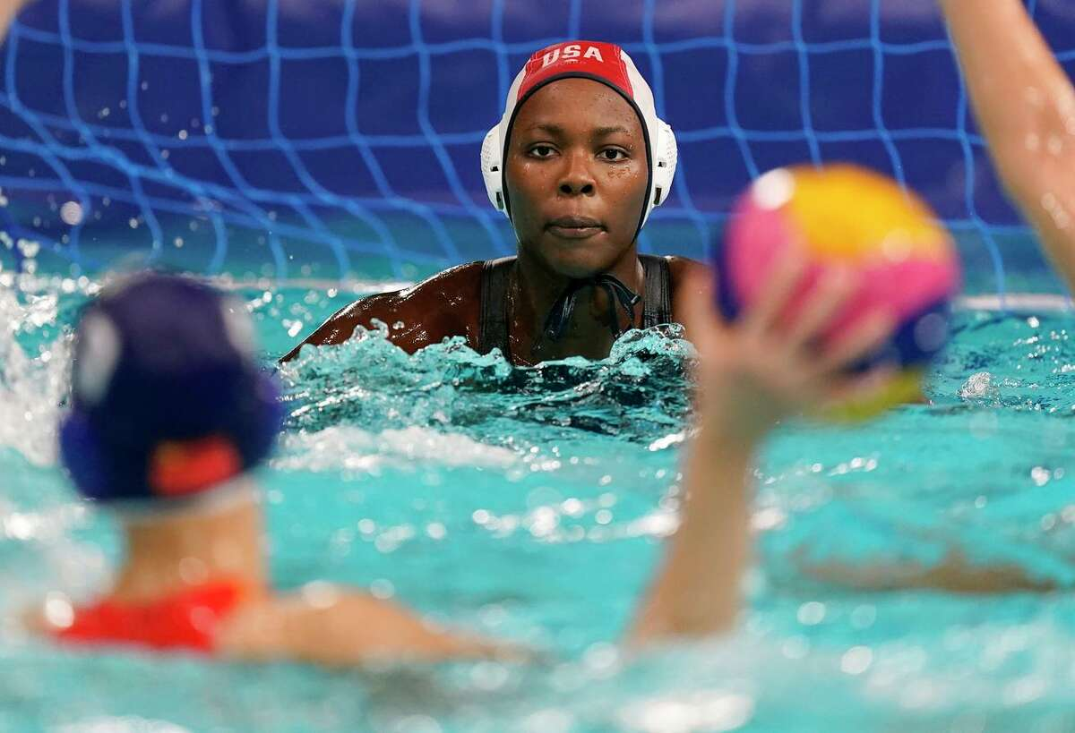 United States goalkeeper Ashleigh Johnson keeps watch on a Chinese player during a preliminary-round women's water polo match in Tokyo. The U.S. won, 12-7.