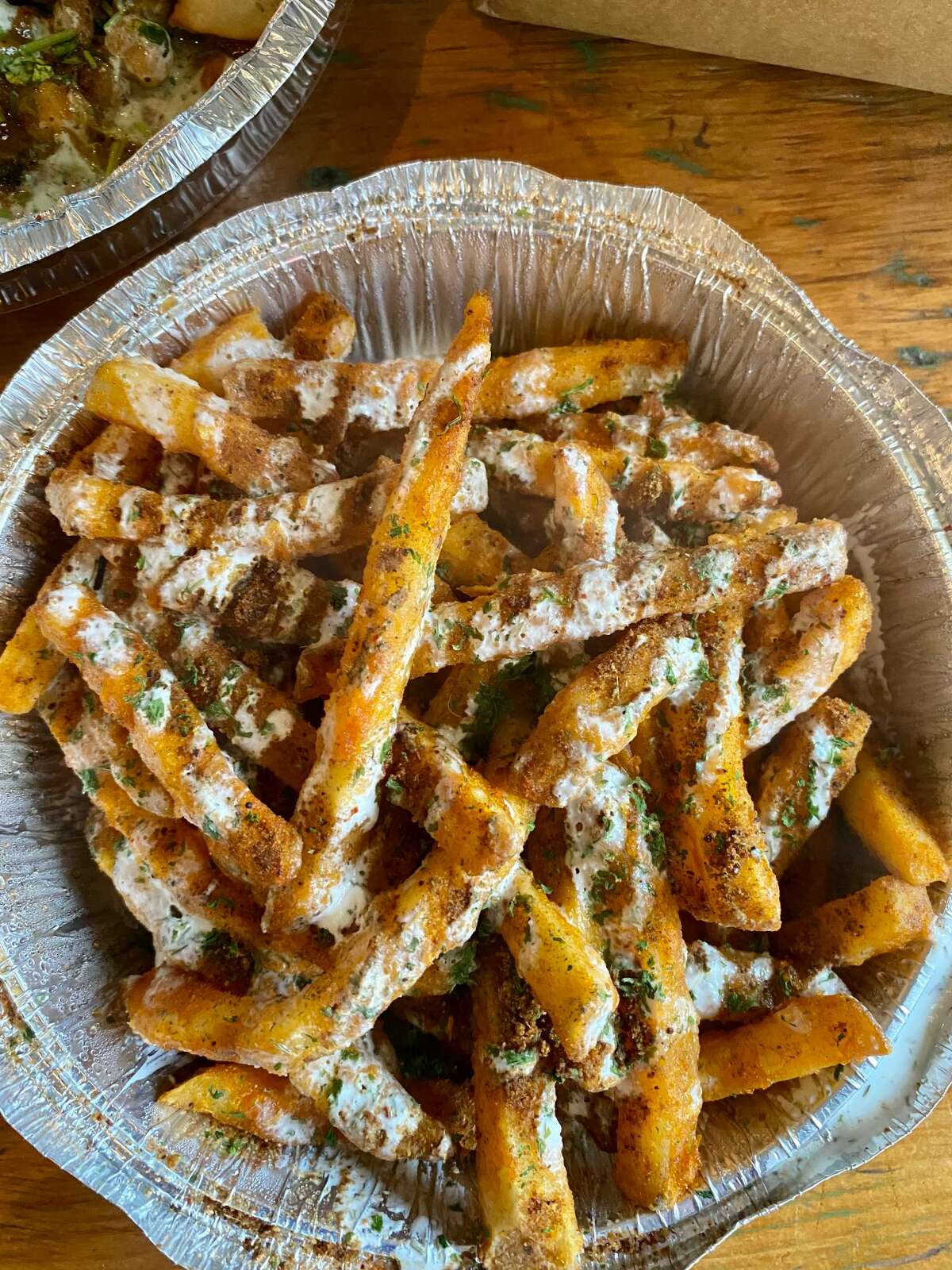 Masala Fries at Alif Cafe in Glens Falls are topped with chaat masala, raita, tamarind chutney and mint chutney. (Susie Davidson Powell/for the Times Union.)