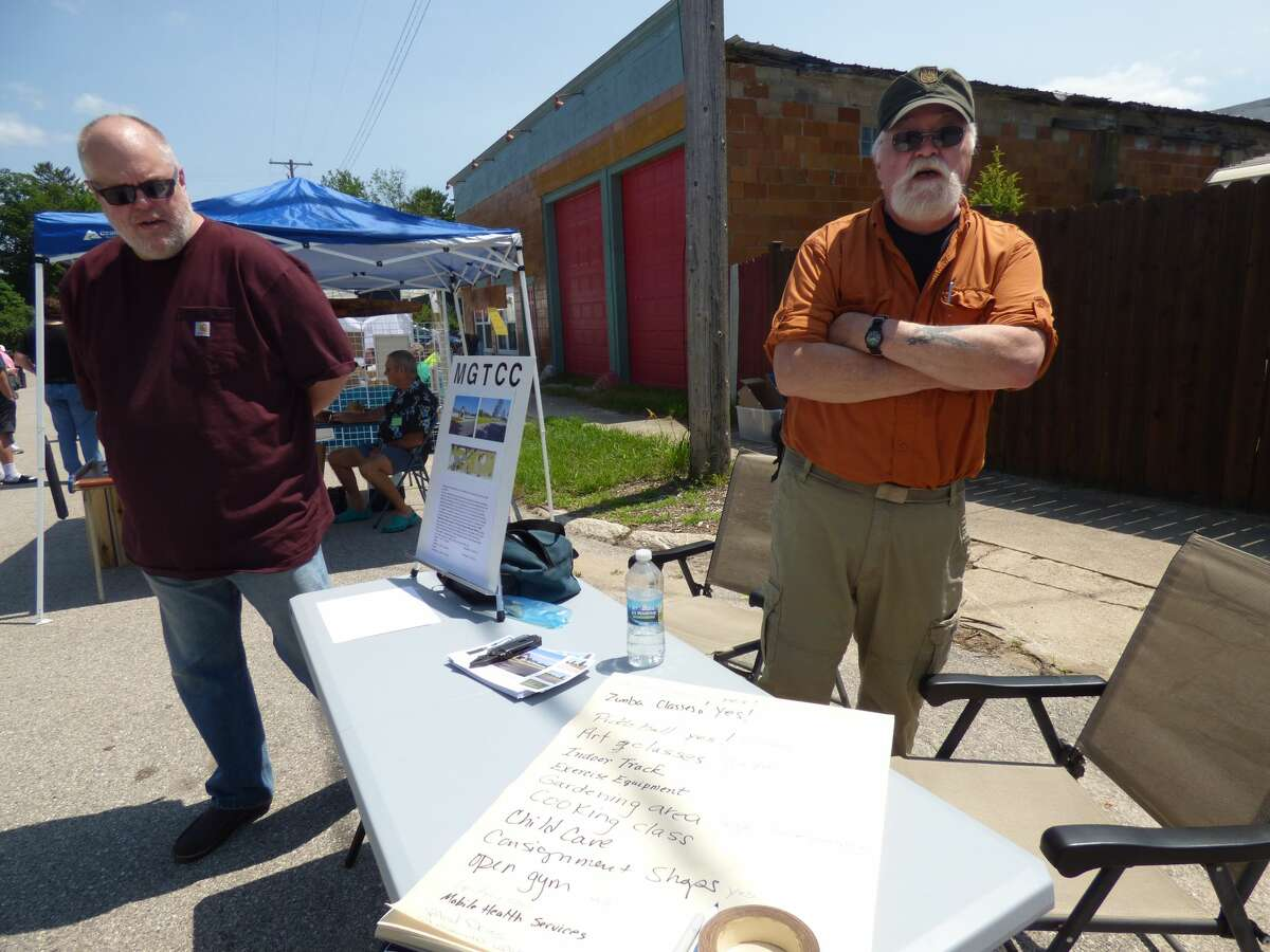 Eric Andersen (left) and Paul Petrovich share information at an arts and crafts show in Kaleva, July 17. Andersen and Petrovich are members of a committee with the aim to acquire a vacant school in Maple Grove Township to convert it into a community center.