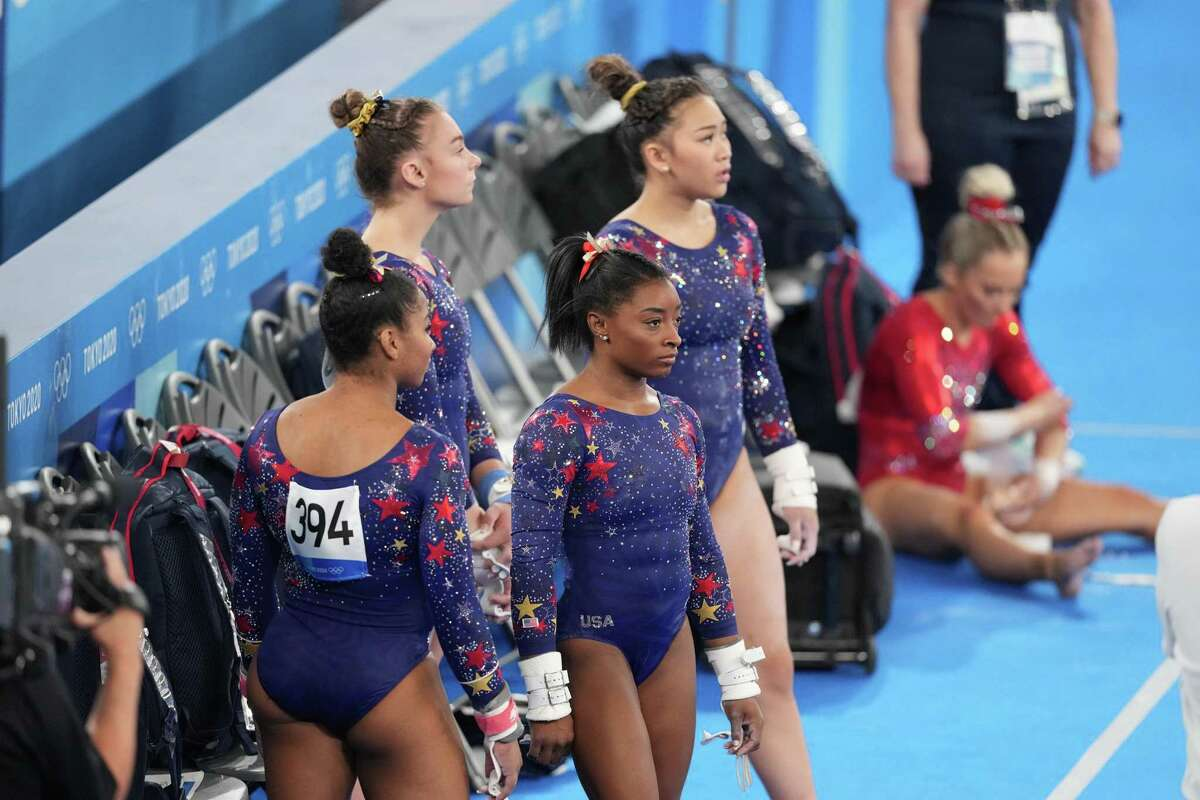 Jordan Chiles, with her back turned away from camera, Simone Biles, center, Grace McCallum and Sunisa Lee, of the United States, wait on the side during women's qualification for the Artistic Gymnastics final at Ariake Gymnastics Center in Tokyo on Sunday, July 25, 2021. (Doug Mills/The New York Times)