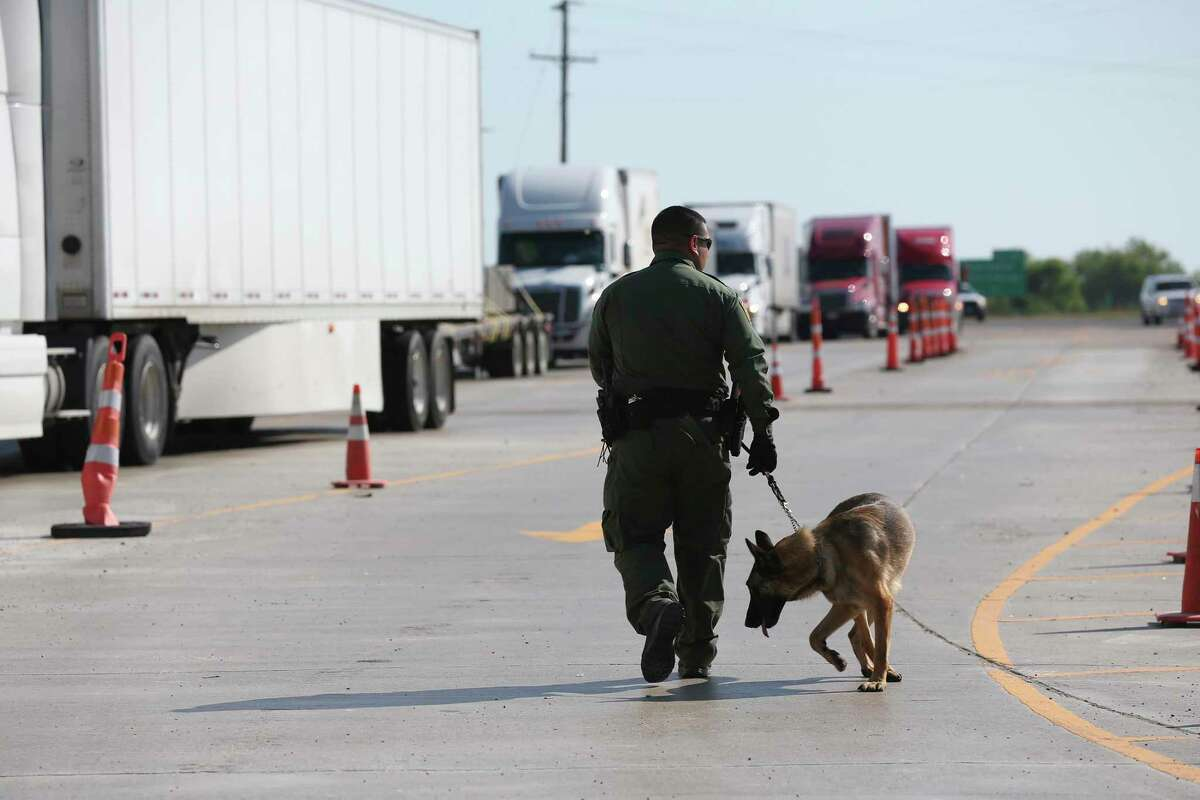 A U.S. Border Patrol K-9 unit works the tractor trailer lane at the Laredo checkpoint near Encinal, Texas in 2018. A Montgomery County man and woman were charged Thursday in federal court for allegedly trying to smuggle 89 people in a tractor trailer north of the U.S.-Mexico border.