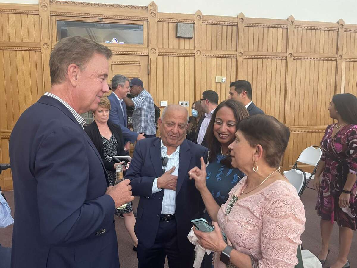 Dr. Manisha Juthani, flanked by her parents, speaks with Gov. Ned Lamont.