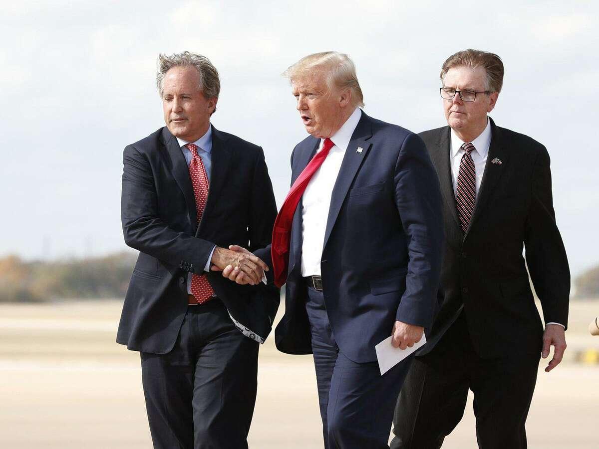 Texas Attorney General Ken Paxton, left, greets President Donald Trump at Austin Bergstrom International Airport in November, with Lt. Gov. Dan Patrick is on the right. (Jay Janner/Austin American-Statesman/TNS)