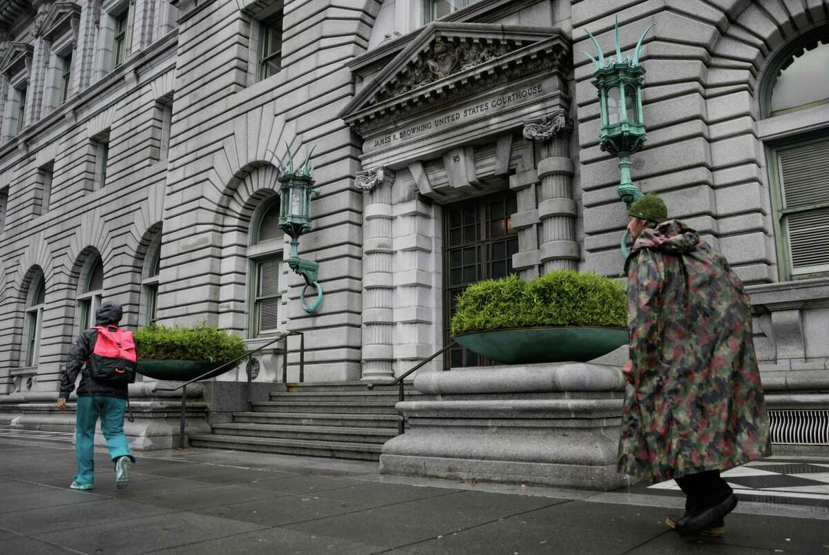 """Pedestrians walk past the Ninth Circuit Court of Appeals in San Francisco. The court said an inmate whose hearing aide batteries weren't replaced for month had adequately alleged """"deliberate indifference"""" to his rights."""