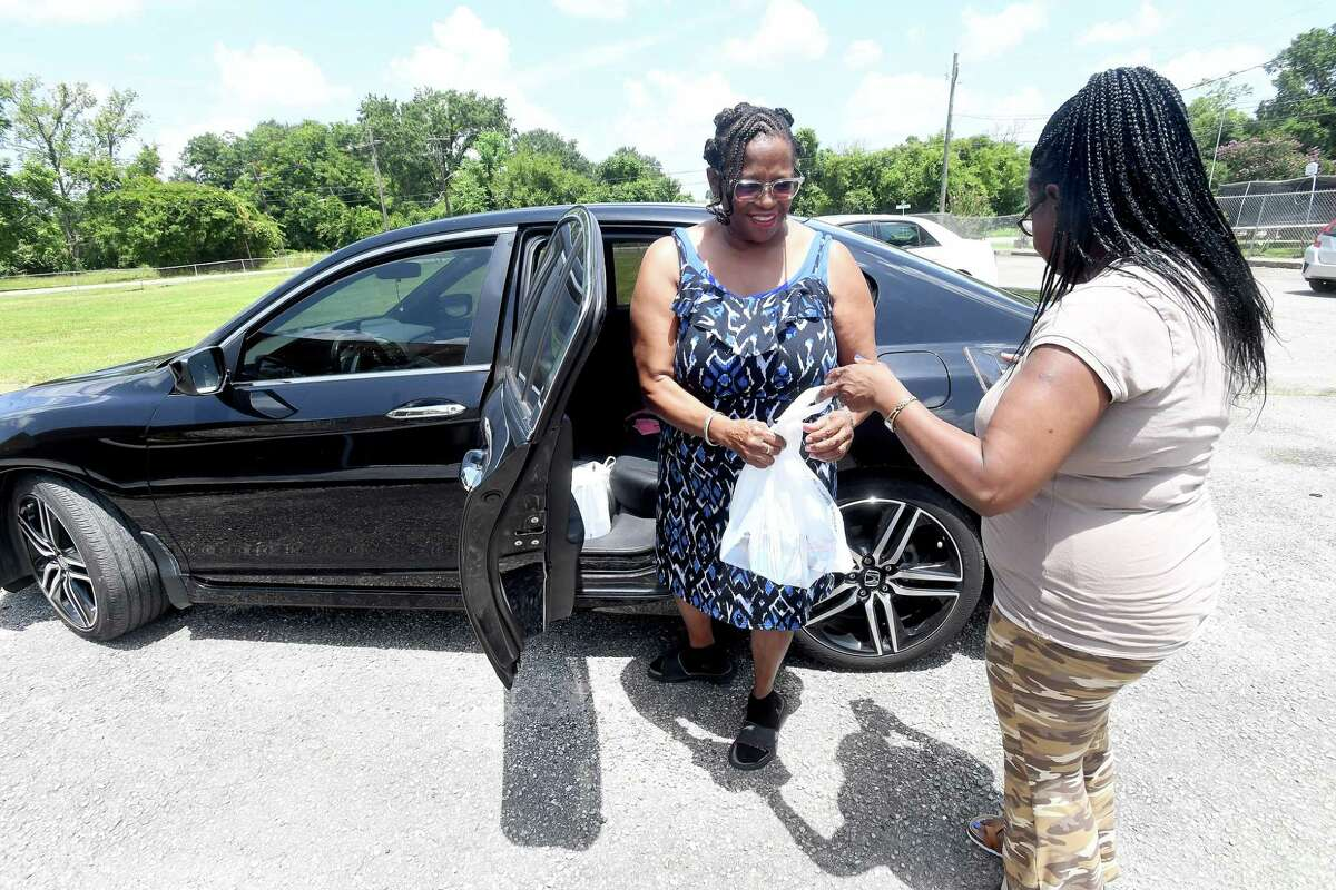 Stacy Smith gets help from Judith Lewis loading bags of meals for her grandchildren and others during the Summer Meals program at St. Luke Missionary Baptist Church Monday. Photo made Monday, July 26, 2021 Kim Brent/The Enterprise