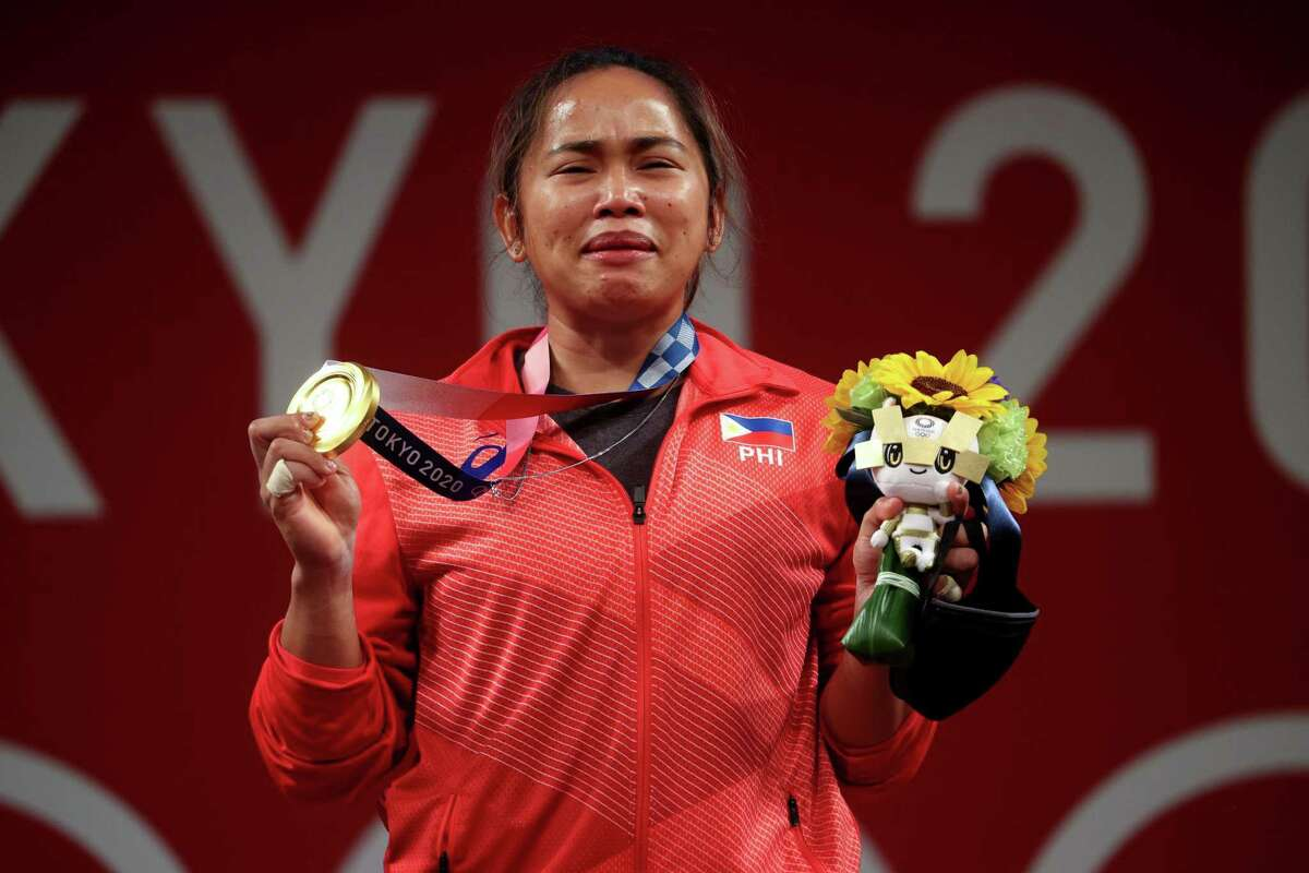 Hidilyn Diaz of the Philippines poses with the gold medal during the medal ceremony.