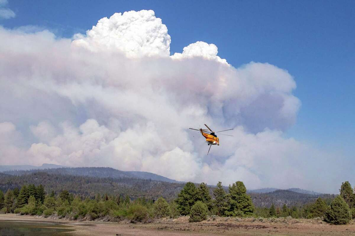A helicopter flies with a load of water to the Bootleg fire, 27 miles northeast of Klamath Falls, near Bly, Oregon, on July 15, 2021. (Payton Bruni/AFP via Getty Images/TNS)