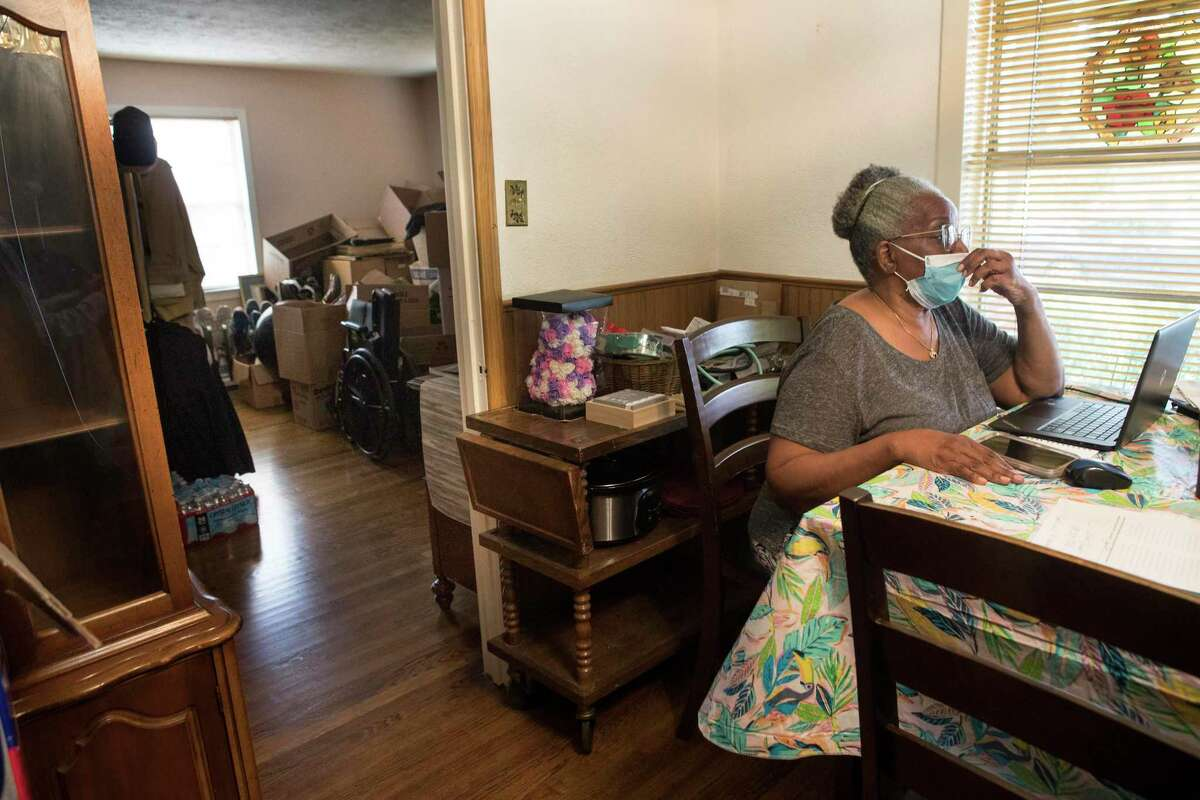 Jaunetta Johns sits at the dining table of her Pleasantville neighborhood home, near the living room filled with boxes and many of her family's possessions Monday, July 26, 2021 in Houston. Her home is slated to be rebuilt as part of a post-Harvey rebuilding program. Many of their possessions are in boxes in their living room, because the rebuild is on hold, because of a dispute with the Texas General Land Office. Mayor Sylvester Turner joined residents of Pleasantville, Sagemont, and other communities urging fairness in the post-Harvey Home rebuilding program through the Texas GLO.