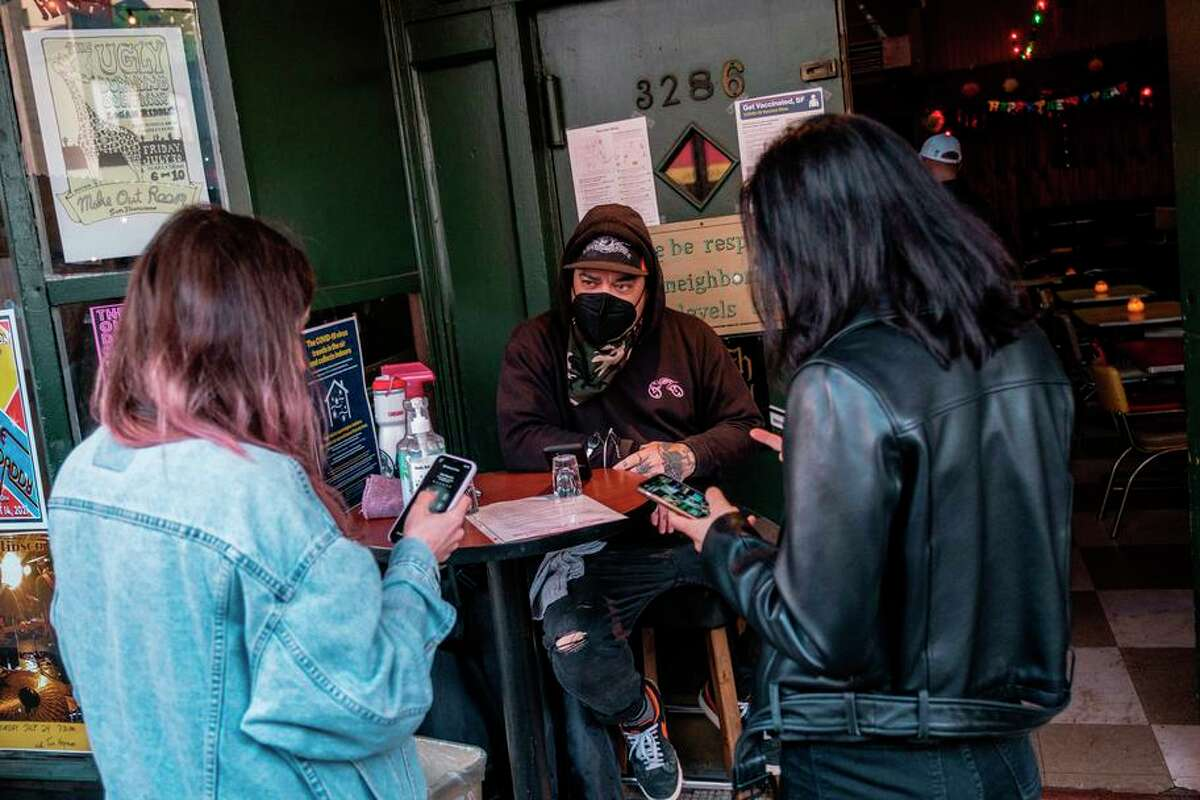 Doorman Jason Voisine waits for two patrons to show him proof of vaccination at the Latin American Club in San Francisco.