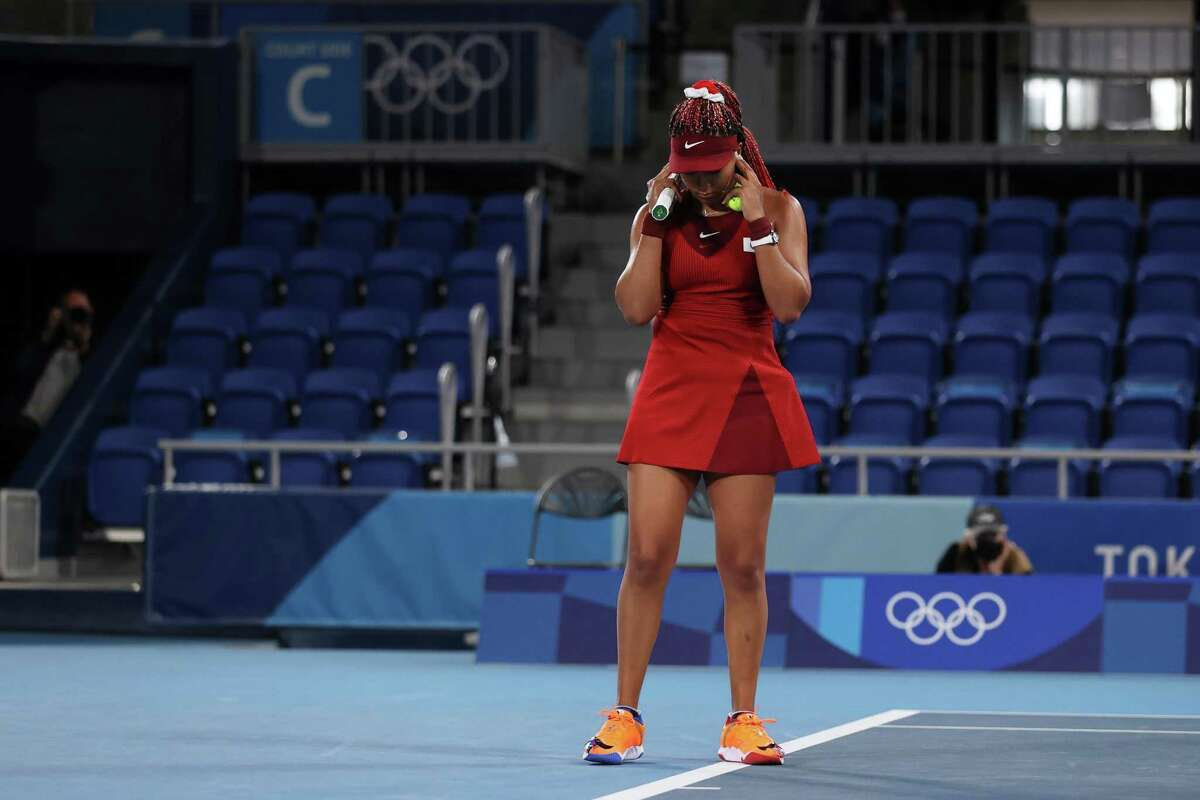 TOKYO, JAPAN - JULY 27: Naomi Osaka of Team Japan covers her ears before match point during her Women's Singles Third Round match against Marketa Vondrousova of Team Czech Republic on day four of the Tokyo 2020 Olympic Games at Ariake Tennis Park on July 27, 2021 in Tokyo, Japan. (Photo by David Ramos/Getty Images)