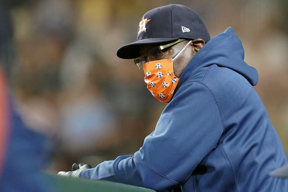 Houston Astros manager Dusty Baker Jr. wears a mask as he looks out from the dugout rail during a baseball game against the Seattle Mariners, Monday, July 26, 2021, in Seattle. (AP Photo/Ted S. Warren)