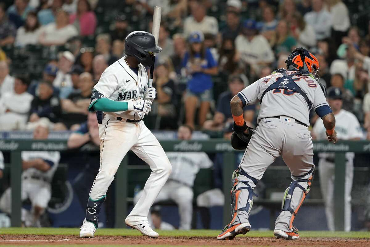 Seattle Mariners' Shed Long Jr., left, watches as Houston Astros catcher Martin Maldonado chases a wild pitch that advanced Mariners' Luis Torrens from first to second base during the sixth inning of a baseball game, Monday, July 26, 2021, in Seattle. Long singled on the at-bat. (AP Photo/Ted S. Warren)