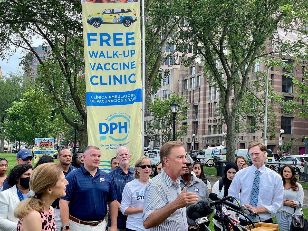 """Gov. Ned Lamont's message to the young and unvaccinated: """"It's about the team. It's not just about you."""" At right is Mayor Justin Elicker. Behind the governor in the blue shirt is Glen Lungarini, the executive director of the Connecticut Interscholastic Athletic Conference."""