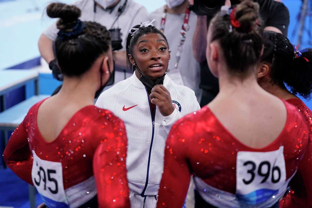 Simone Biles, of the United States, talks to teammates during the artistic women's team final at the 2020 Summer Olympics, Tuesday, July 27, 2021, in Tokyo.