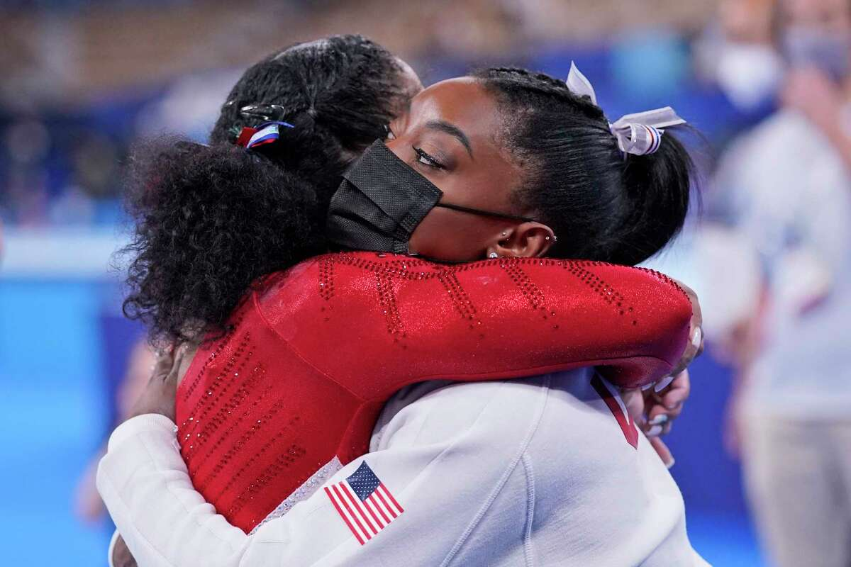Simone Biles, of the United States, embraces teammate Jordan Chiles after she exited the team final with apparent injury, at the 2020 Summer Olympics, Tuesday, July 27, 2021, in Tokyo. The 24-year-old reigning Olympic gymnastics champion Biles huddled with a trainer after landing her vault. She then exited the competition floor with the team doctor.
