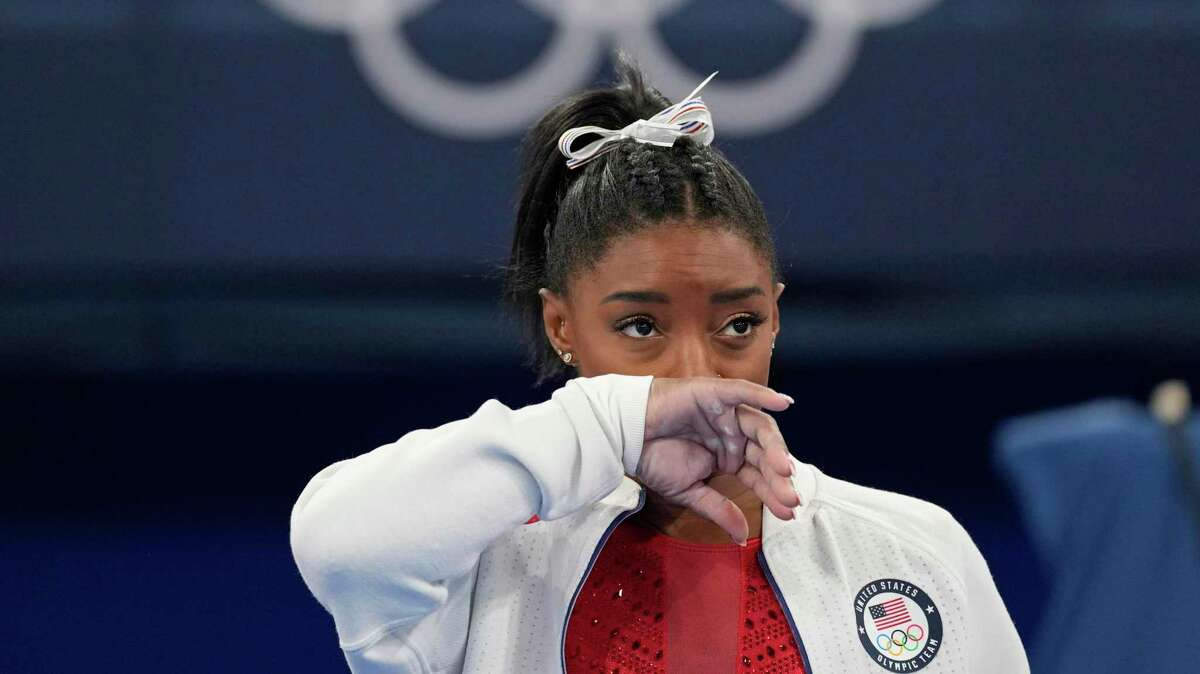 Simone Biles, of the United States, watches gymnasts perform after she exited the team final at the 2020 Summer Olympics, Tuesday, July 27, 2021, in Tokyo.