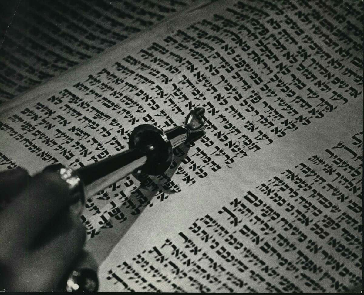 A person uses a pointer to read a selection in the Torah.