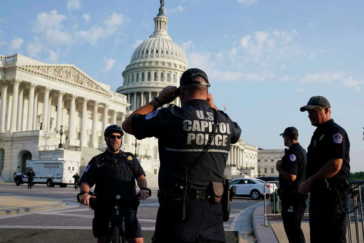 The U.S. Capitol is seen in Washington, early Tuesday, July 27, 2021, as U.S. Capitol Police watch the perimeter. Democrats are launching their investigation into the Jan. 6 Capitol insurrection. They're beginning with a focus on the law enforcement officers who were attacked and beaten as the rioters broke into the building. It's an effort to put a human face on the violence of the day. The police officers who are testifying Tuesday endured some of the worst of the brutality. The panel's first hearing comes as partisan tensions have only worsened since the insurrection. Many Republicans have played down or outright denied the violence that occurred and denounced the Democratic-led investigation as politically motivated.