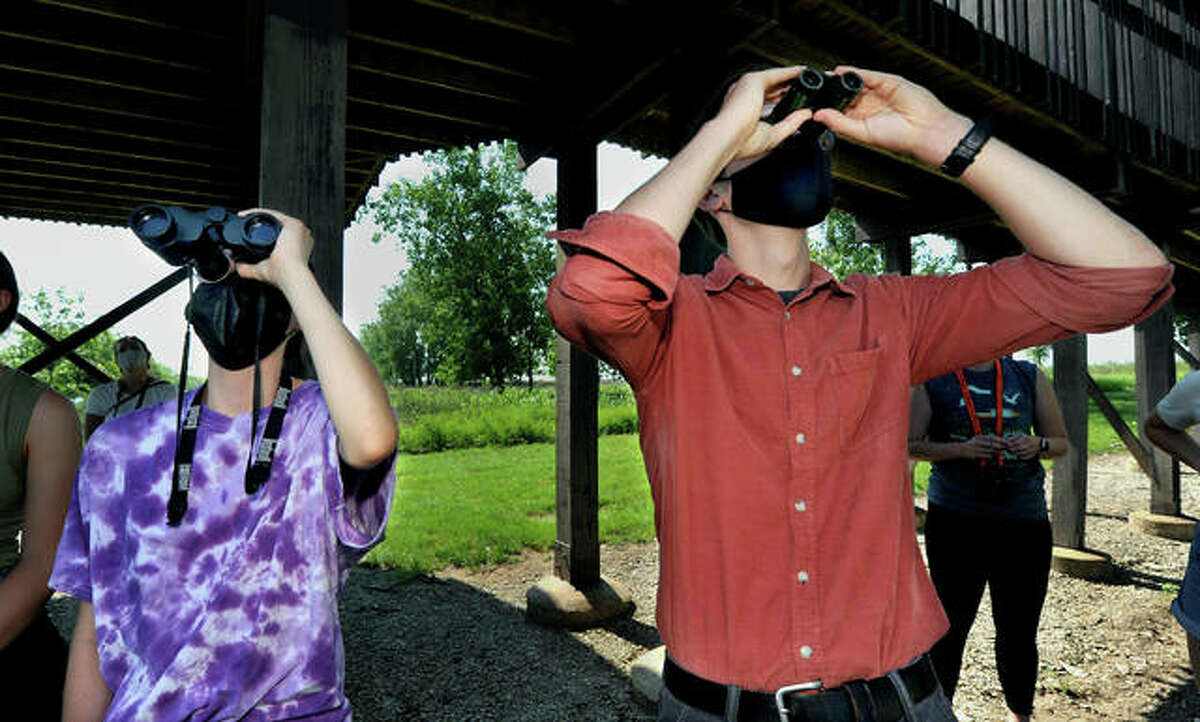 Natalie Wagner, left, of St. Louis, and Cole Filges, of Collinsville, watch as a blue heron flies over during a tour at the Audubon Center at Riverlands Monday.