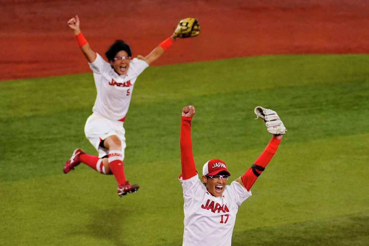 Japan's Yukiko Ueno (17) and Yu Yamamoto (5) celebrates after a softball game against the United States at the 2020 Summer Olympics, Tuesday, July 27, 2021, in Yokohama, Japan. Japan won 2-0.
