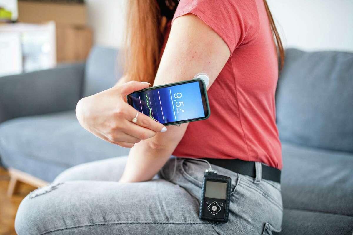 A woman swipes a sensor to determine glucose measurement.