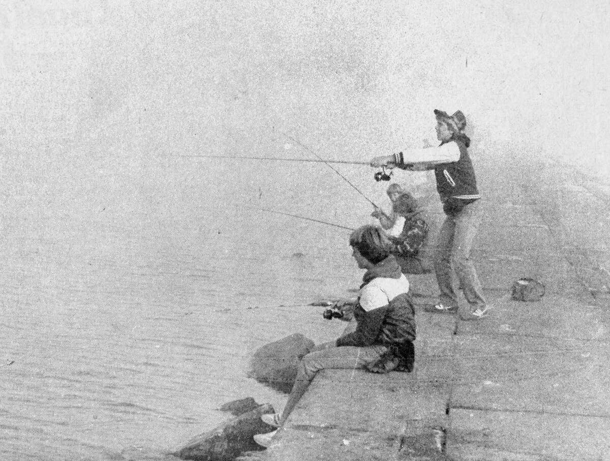 This morning's chilly temperatures and creeping fog failed to deter these young fishermen who spent the morning casting for salmon off First Street Pier. Joe O'Hagan stands and tosses his line into the water while (sitting, front to back) John O'Hagan, Ricky Pohl and Danny Pachesny also try their luck. Several chinook salmon and lake trout were reported caught this morning from the pier. The photo was published in the News Advocate on July 29, 1981. (Manistee County Historical Museum photo)