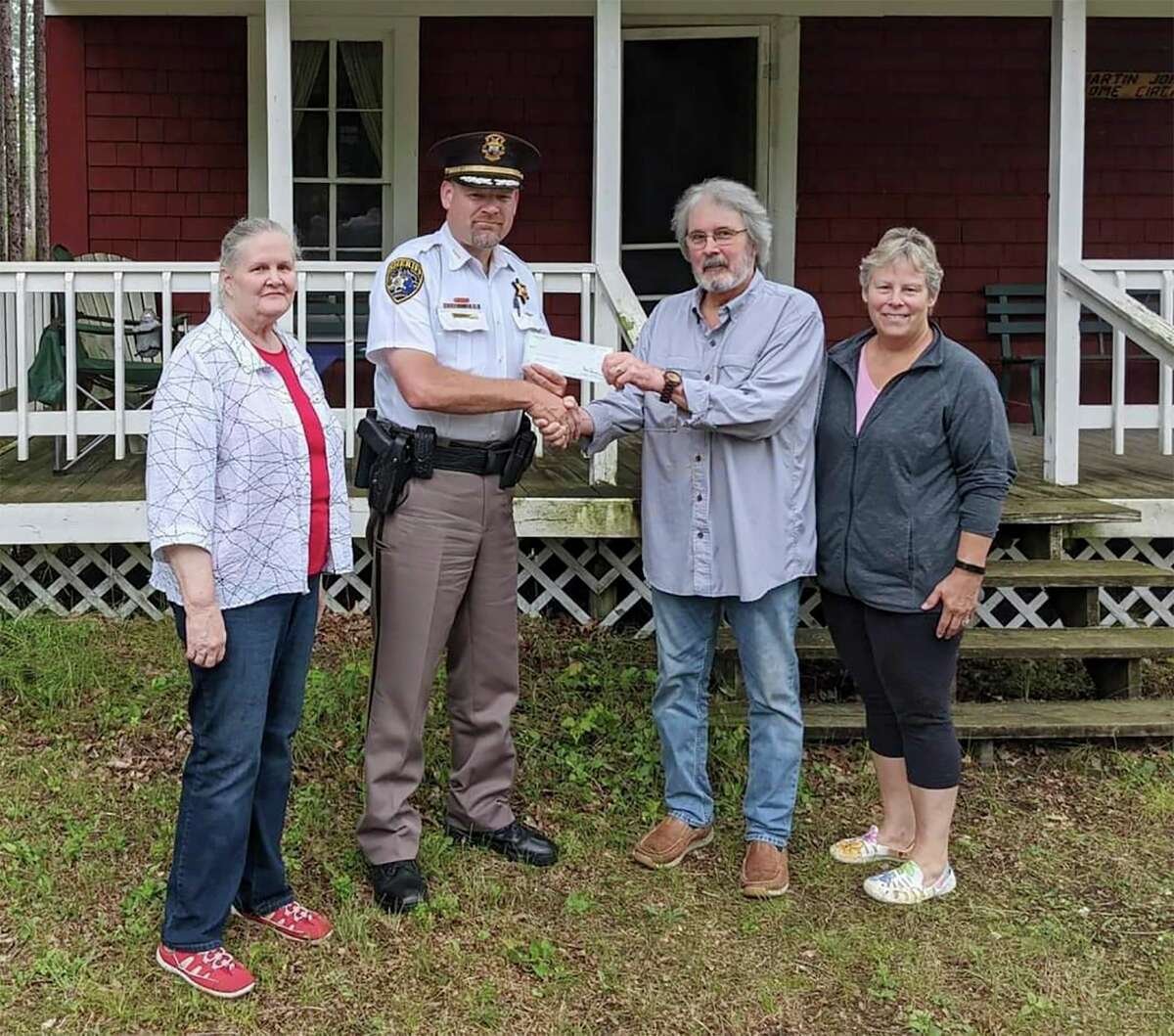 Lake County Sheriff Rich Martin presents a check for $1,000 totheMartin Johnson Heritage Museum in Irons. (Courtesy/Lake County Sheriff's Office)