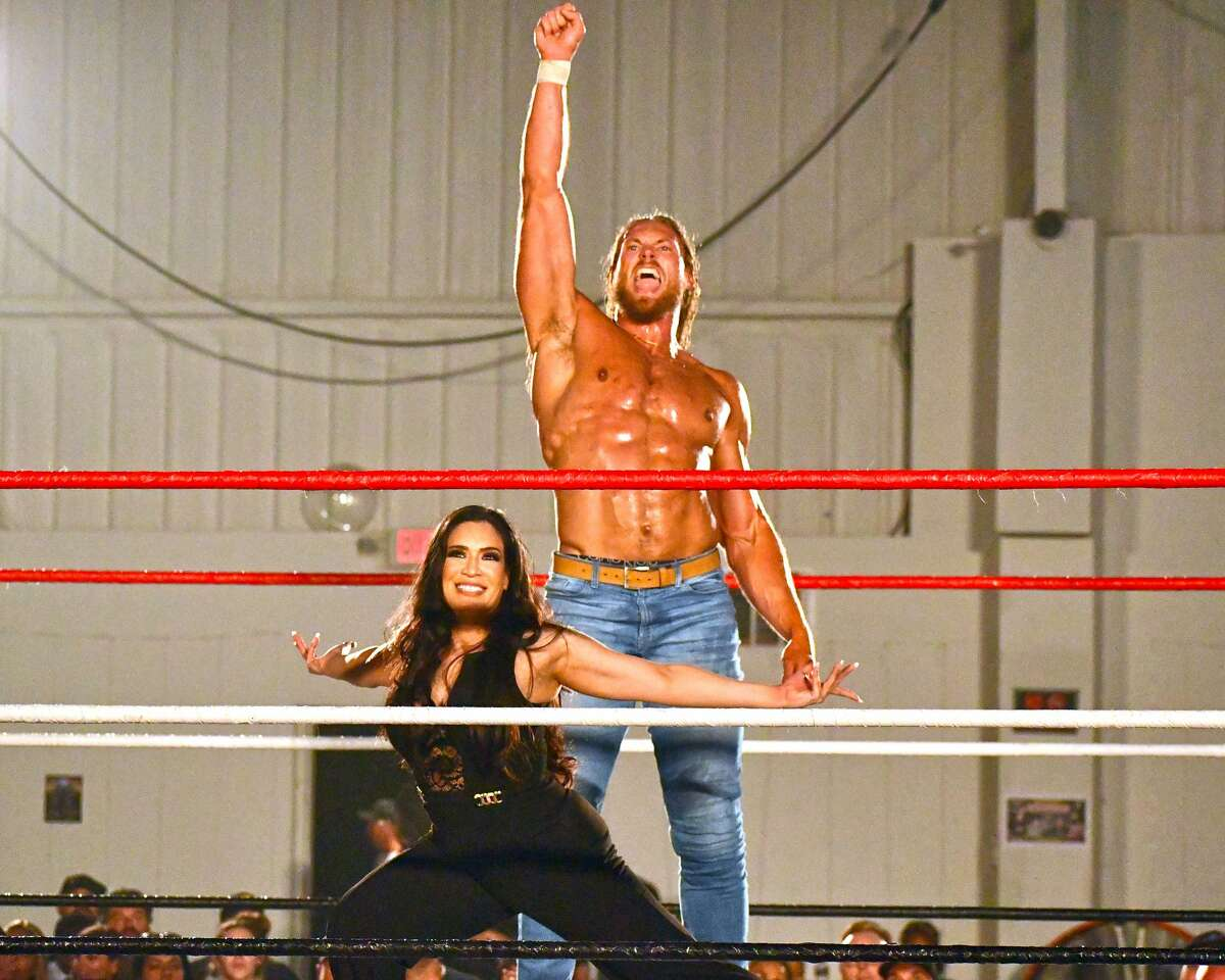Big Caz XL and his manager Melina pose for the crowd after his victory over Alex Arsenal during SWE Fury's West Texas Fury Fest on Saturday in the Prima Vista Events Center in Lubbock.