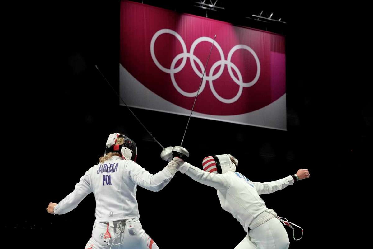 Warren graduates Kelley Hurley, right, competing against Poland's Ewa Trzebinksa in women's team epee Tuesday, and sister Courtney have dedicated themselves to the sport of fencing since they were middle schoolers in San Antonio.