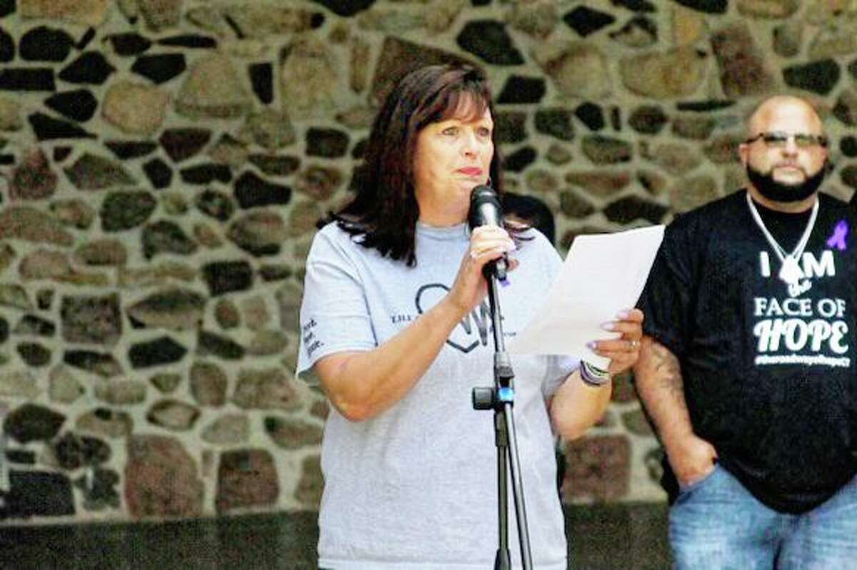 Ann Lindstrom, founder of T.H.E. Movement, speaks on International Overdose Awareness Day with fellow founder and Executive Director Domenick Galarneau in the background.