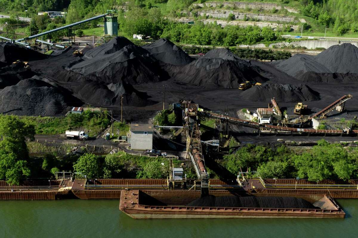 Coal is loaded onto a barge in Belle, W.Va. The Biden administration will revise a Trump-era rule that allowed many coal-fired power plants to avoid or delay installing equipment that could prevent lead, selenium and other toxic pollutants from seeping into rivers and streams, the Environmental Protection Agency announced Monday, July 26, 2021.