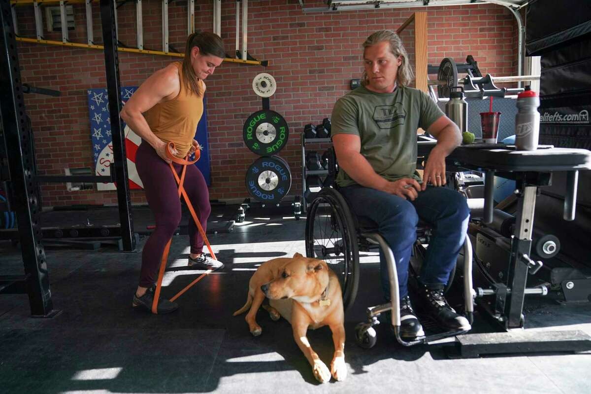 With her husband Sam Willoughby looking on, Alise Willoughby works out at their home.