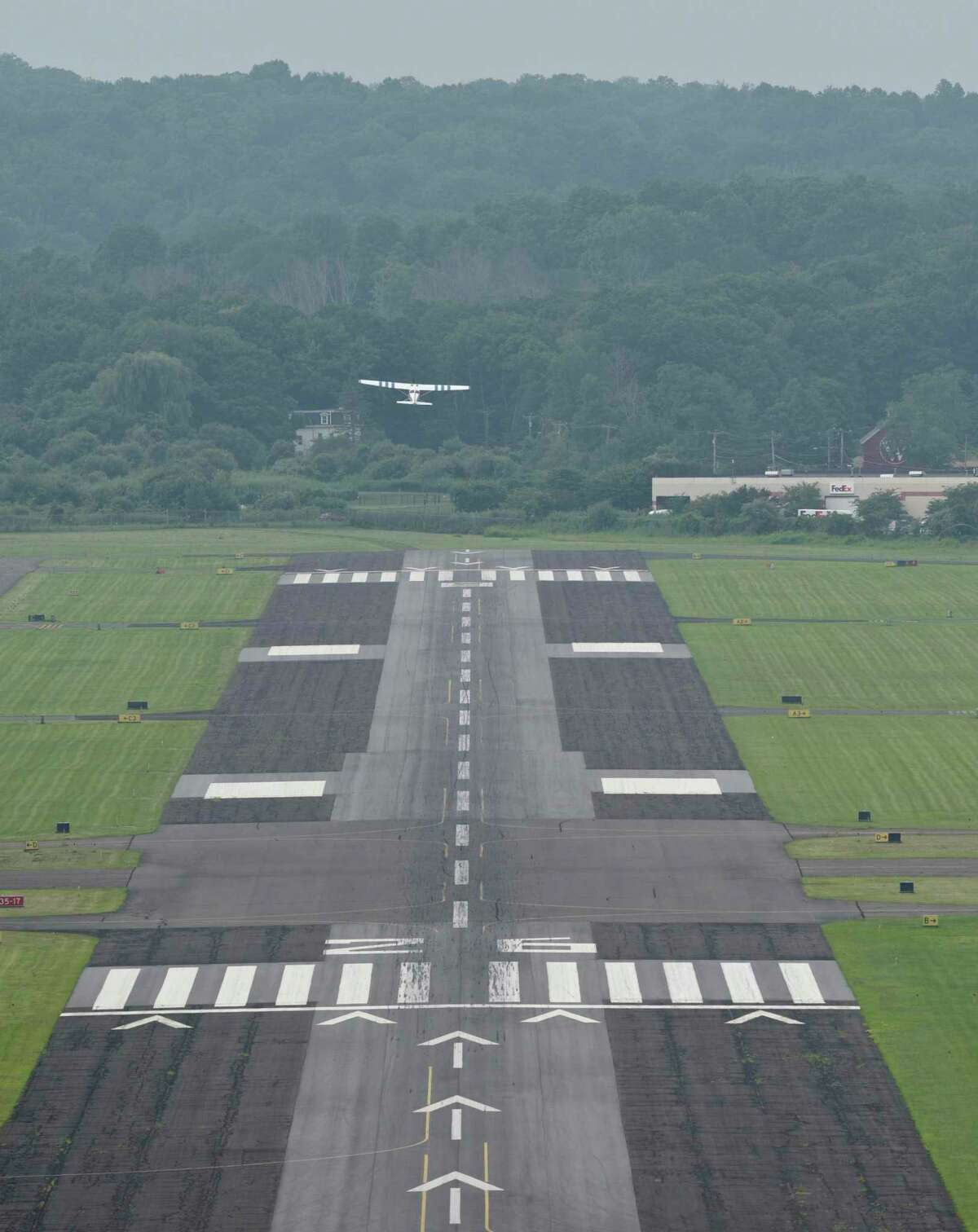An airplane takes off from Danbury Municipal Airport into hazy skies on July 21 in Danbury, .