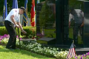 Veteran Sam Jacobellis, of Danbury, places a rose on the Korean War Memorial in memory of Lee R. Hartell, 1st Lt USA KIA, 27 Aug 1951, Medal of Honor, at the Greater Area Korean War Veterans Assoc. ceremony to mark the 68th anniversary of the end of the Korean War. Rogers Park. Tuesday, July 27, 2021, in Danbury, Conn.