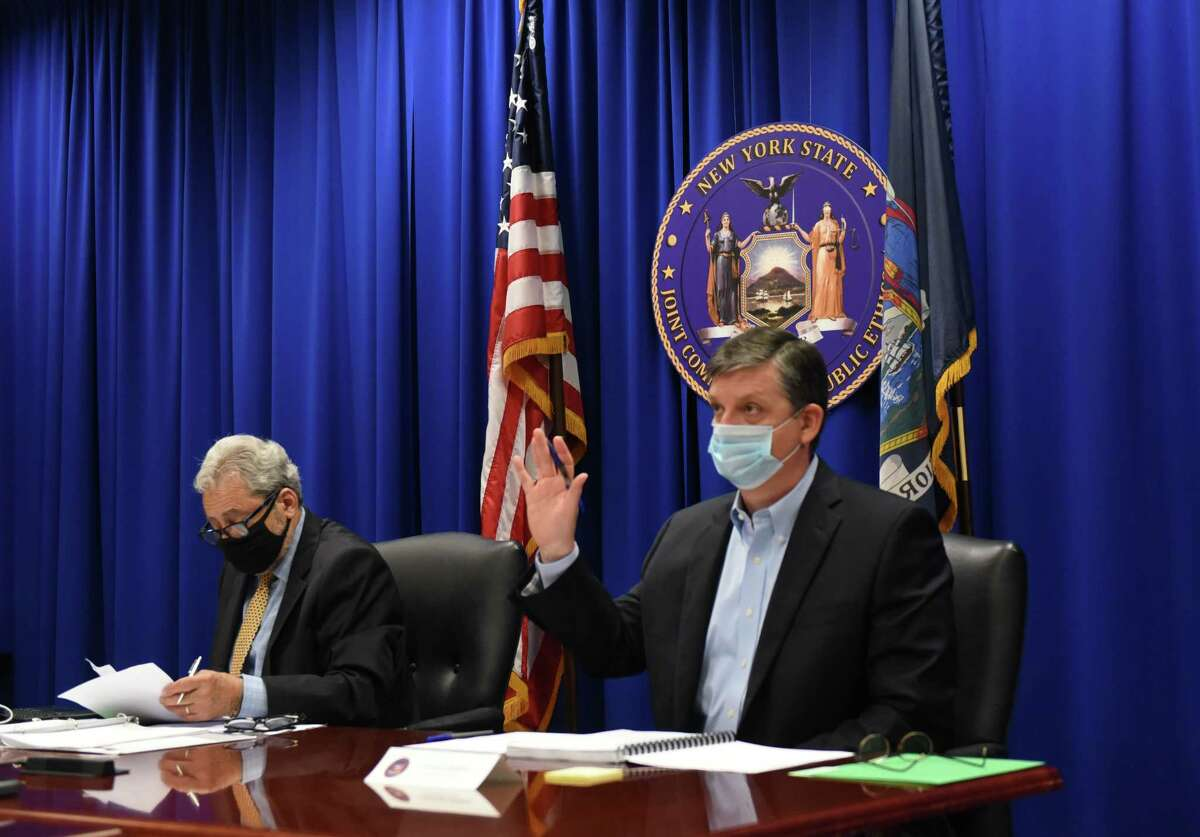 New York State Joint Commission on Public Ethics Commissioner James Dering, right, raises his hand during a vote to move the public portion of the meeting to executive session on Tuesday, July 27, 2021, at the JCOPE offices in Albany, N.Y.