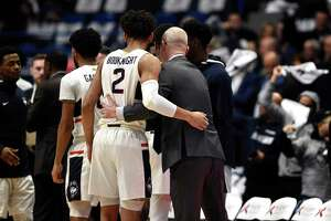 Connecticut's James Bouknight and Connecticut head coach Dan Hurley embrace in the first half of an NCAA college basketball game, Wednesday, Feb. 26, 2020, in Hartford, Conn. (AP Photo/Jessica Hill)