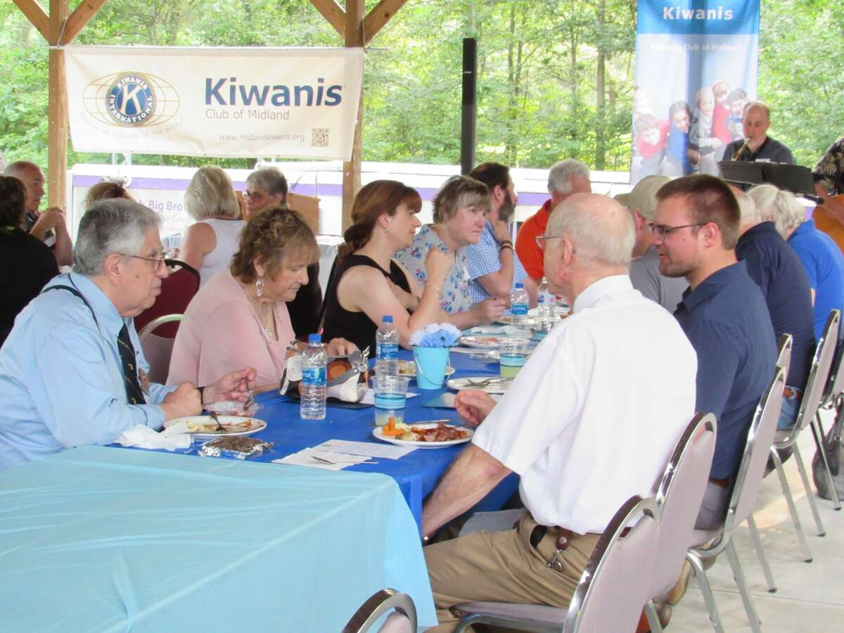 Kiwanis members and supporters chat over a barbeque dinner at Midland Kiwanis Club's 100th anniversary celebration on Monday, July 26.