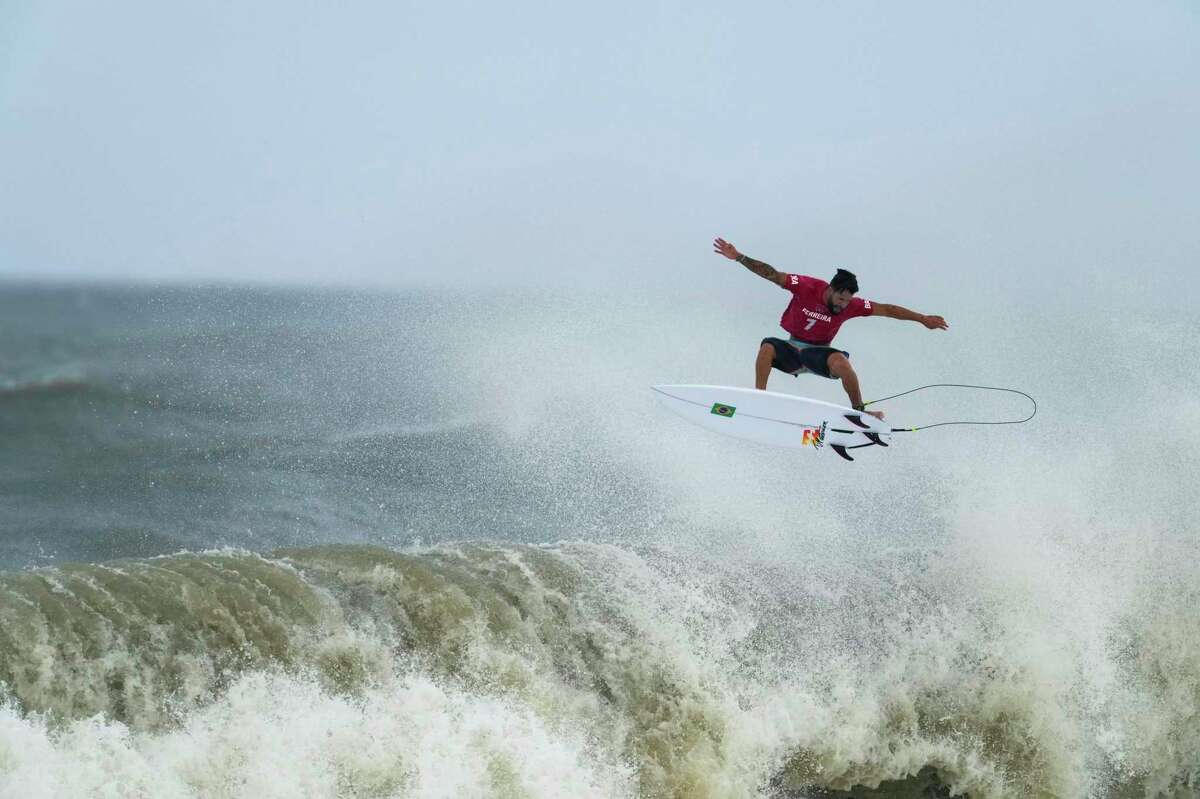 Brazil's Italo Ferreira goes to the air on a wave during the semifinals of the men's surfing competition at the 2020 Summer Olympics, Tuesday, July 27, 2021, at Tsurigasaki beach in Ichinomiya, Japan. Ferreira won the gold medal. (AP Photo/Francisco Seco)