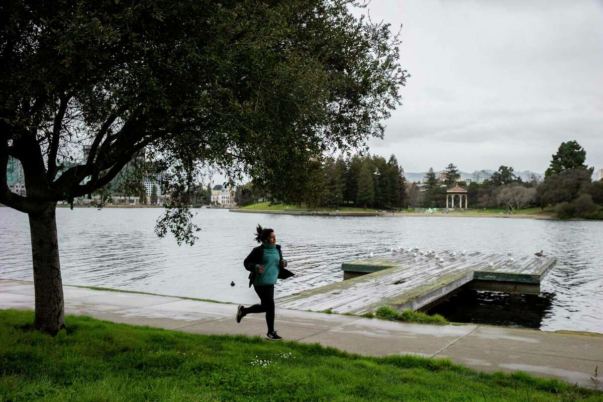 A person runs at Lake Merritt in drizzling rain, Tuesday, Jan. 26, 2021, in Oakland, Calif. A tiny amount of rain that drizzled over the Bay Area garnered an outsize amount of attention from residents of the critically parched region Tuesday.