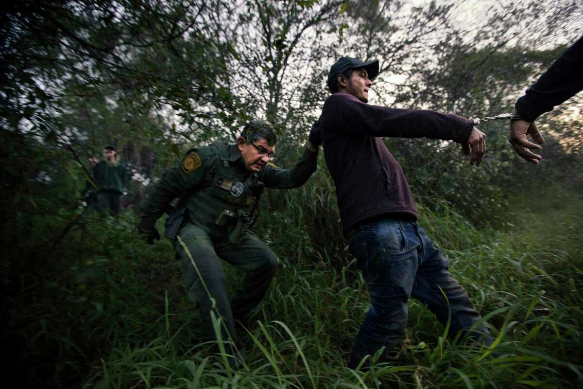 U.S. Customs and Border Protection officers take a group of immigrants to be processed after they tried to avoid arrest hiding in the bushes, Thursday, Dec. 13, 2018, in Mission. The five young men were intercepted in an area without a fence along the border.