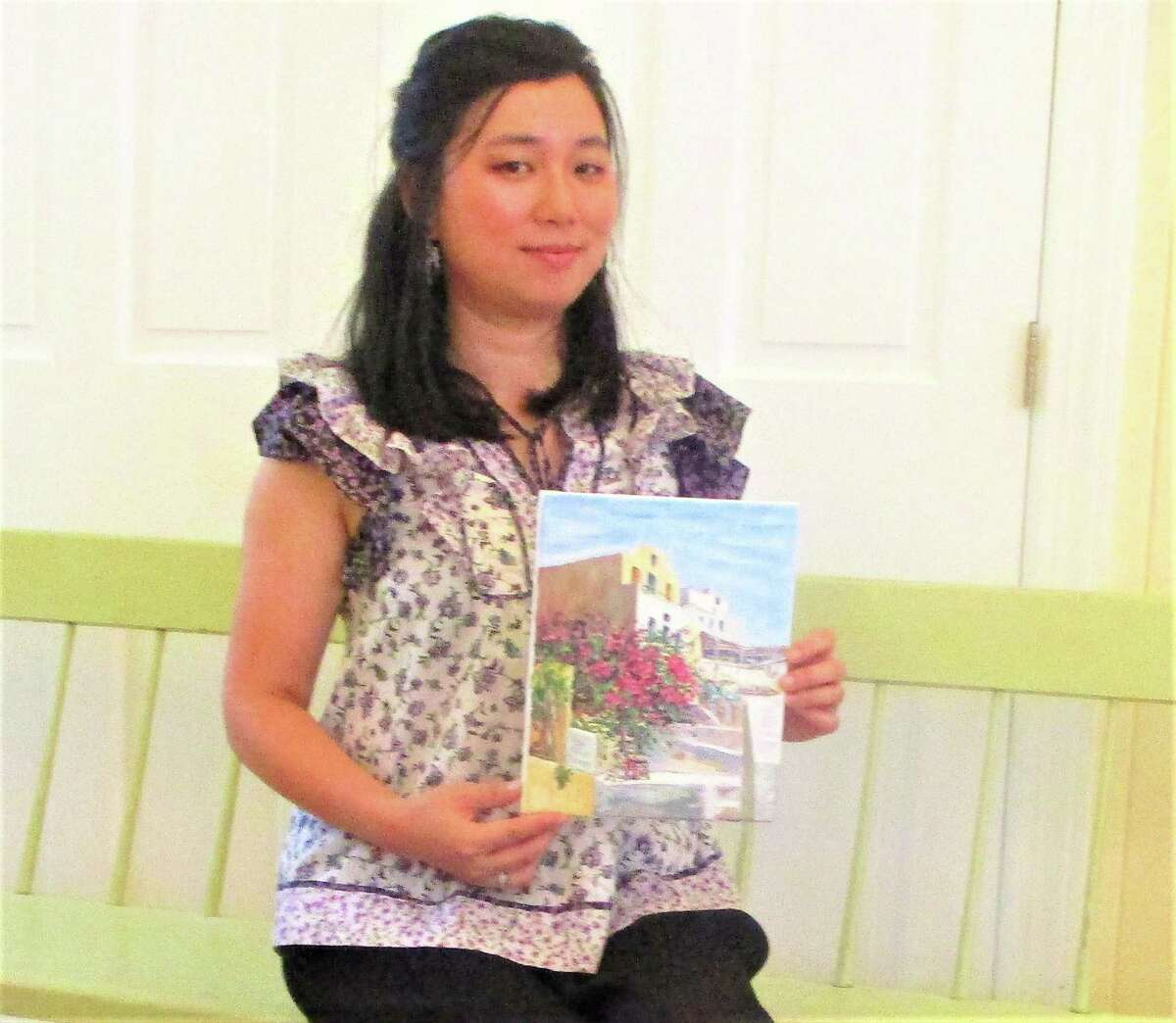Artist Ann Peng holds a painting of a trip to Greece.