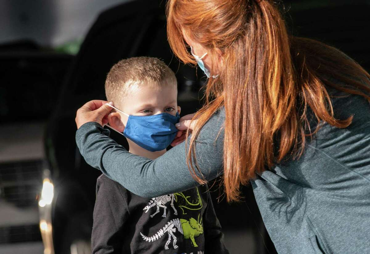 A teacher puts on a child's mask upon his arrival at Stark Elementary School on September 16, 2020 in Stamford, Connecticut.