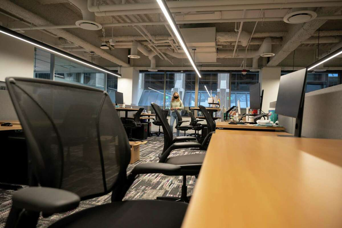 Olga Meleshko, Metromile's manager of executive administration, prepares the auto insurance company's deserted San Francisco office in April for employees to return. Many employers want workers back in the office despite a surge in COVID-19 due to the delta variant.