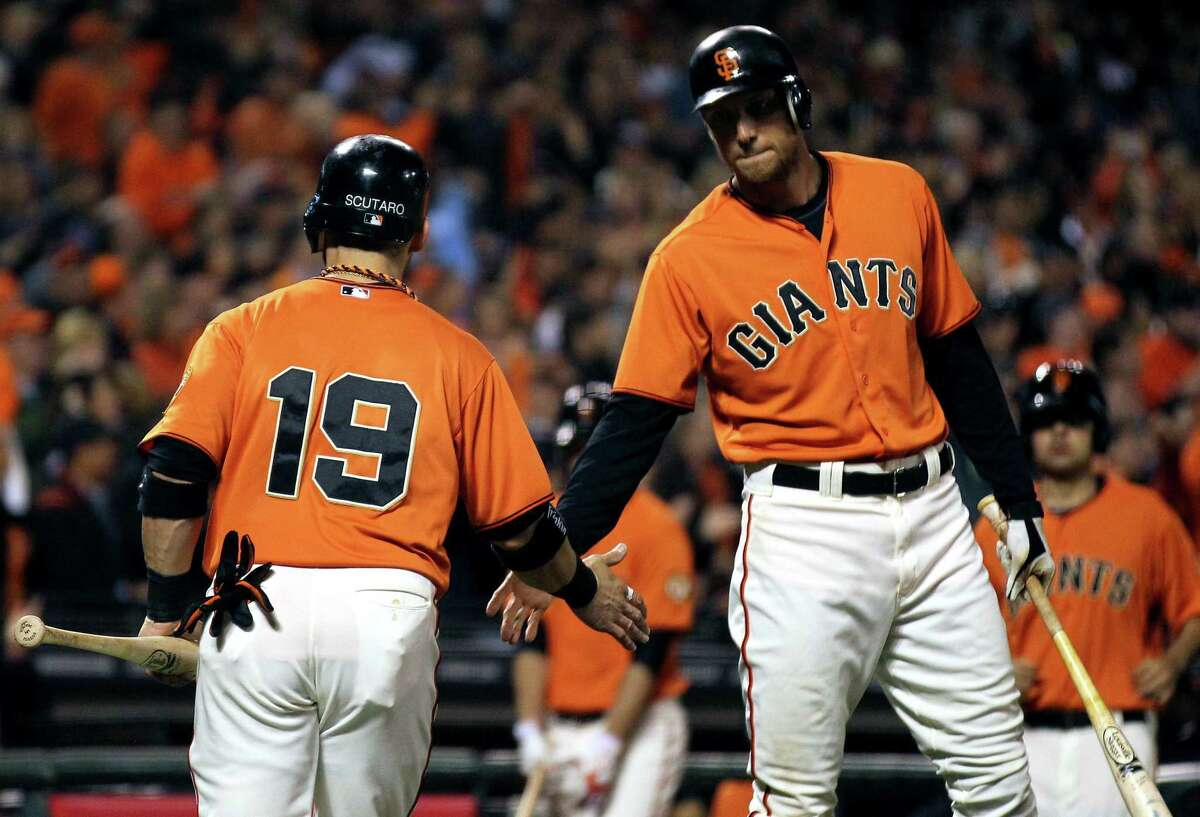 San Francisco Giants Marco Scutaro is greeted by Hunter Pence after Scutaro scored against the San Diego Padres Friday September 21, 2012. in San Francisco California.