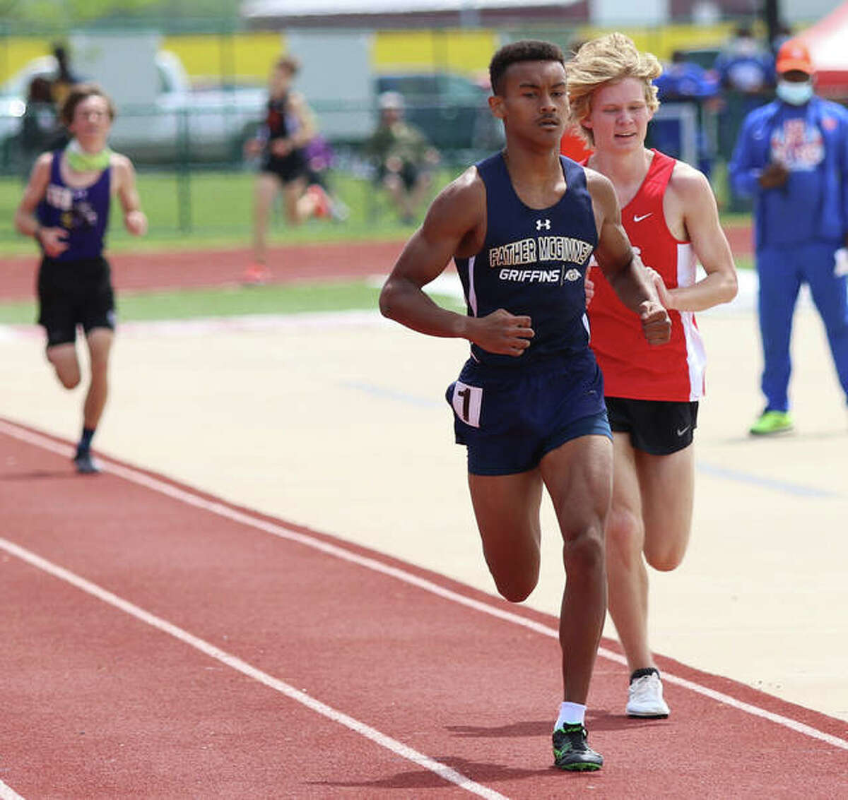 Father McGivney senior Tyler Guthrie laps another runner near finish line of the 3,200-meter run at the Norm Armstrong Invitational at Belleville West High School.
