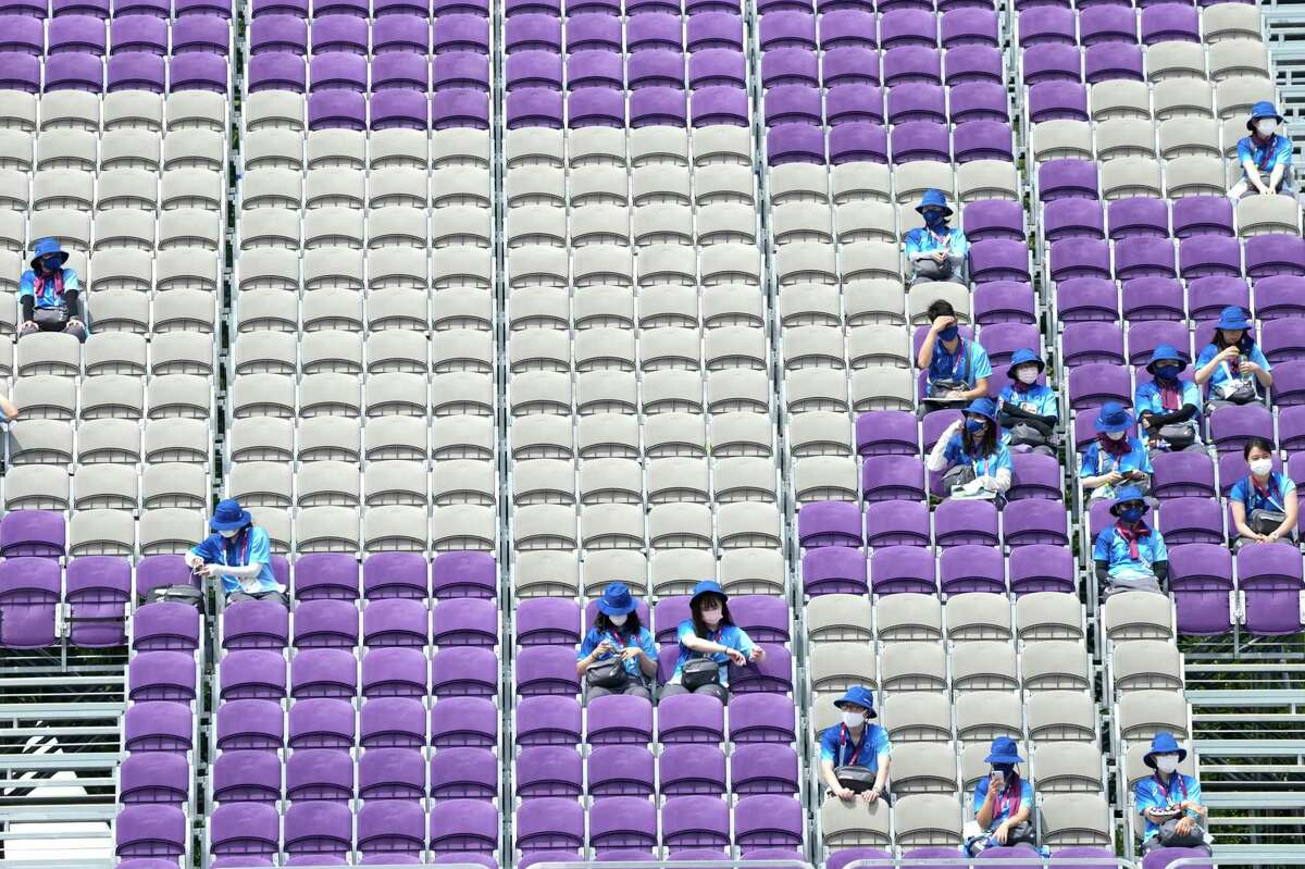 Volunteers seats on empty stands during the men's team competition at the 2020 Summer Olympics, Monday, July 26, 2021, in Tokyo, Japan. (AP Photo/Alessandra Tarantino)