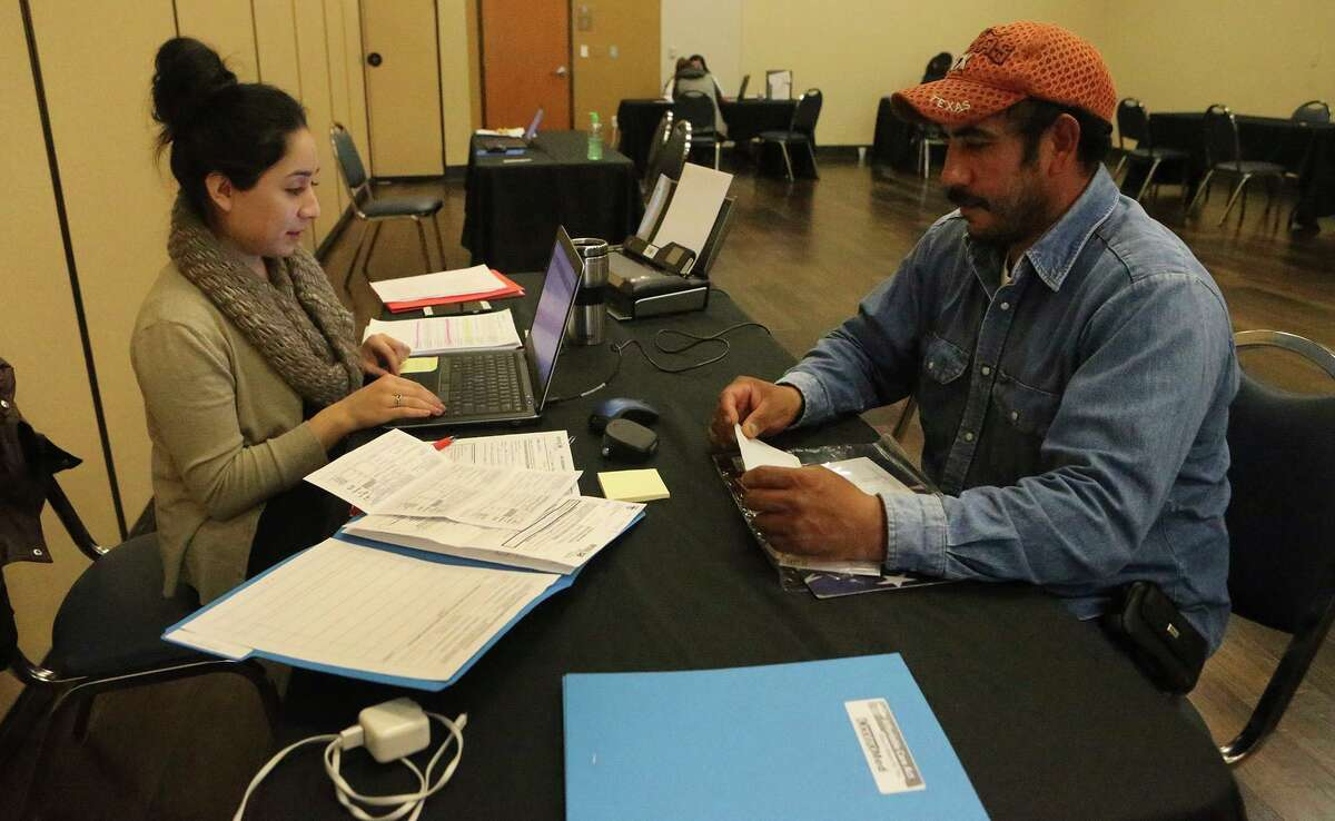 Jeanette Perez, left, helps Manuel Hernandez with the health insurance application process in January 2017 at CentroMed on San Antonio's South Side.